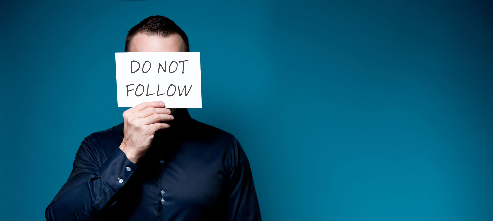 "Man covering his face with a ""Do Not Follow"" sign"